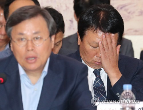 暗い表情でうつむく野球韓国代表の宣銅烈監督(右)=10日、ソウル(聯合ニュース)