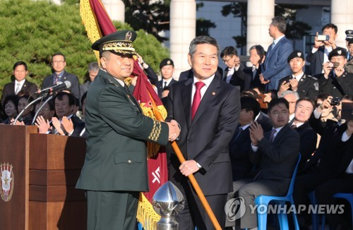10月11日上午,在韩国国防部,新任联参议长朴汉基从防长郑景斗手中接过军旗。(韩联社)
