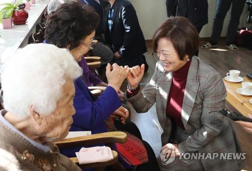 慰安婦被害者と指切りしながら問題解決を約束する陳長官(右)=11日、広州(聯合ニュース)