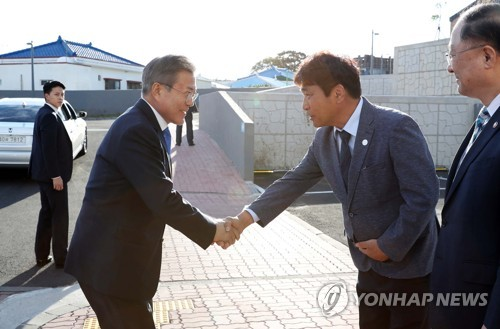 President Moon Jae-in (L) shakes hands with the head of  Gangjeong, a small fishing town on the southern coast of Jeju Island, as he meets with local residents on Oct. 11, 2018. (Yonhap)