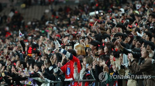 South Korean football fans take photos of national football team players with their smartphones after a friendly match between South Korea and Uruguay at Seoul World Cup Stadium in Seoul on Oct. 12, 2018. (Yonhap)