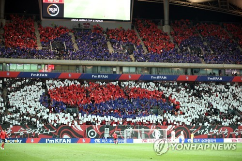 This file photo taken on Oct. 12, 2018, shows South Korean football fans doing a card stunt showing the national flag during the friendly football match between South Korea and Uruguay at Seoul World Cup Stadium in Seoul. (Yonhap)