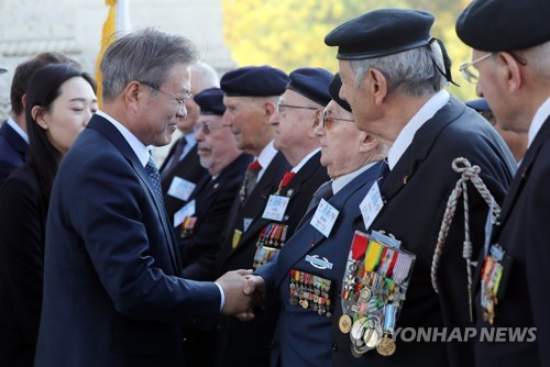 South Korean President Moon Jae-in (L) shakes hands with a French Korean War veteran during an official welcome ceremony held in Paris on Oct. 15, 2018 to mark his four-day state visit to France. (Yonhap)