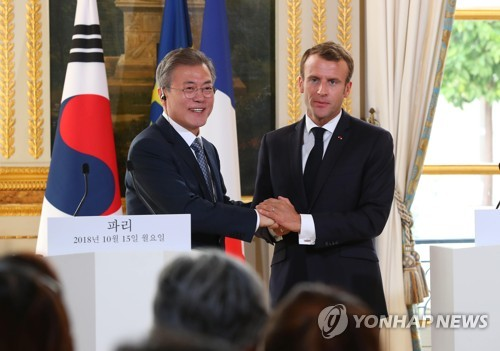 South Korean President Moon Jae-in (L) and French President Emmanuel Macron clasp hands after holding a joint press conference to announce the outcome of their bilateral summit held at the Elysee Palace in Paris on Oct. 15, 2018. (Yonhap)
