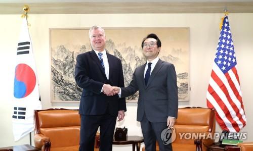 10月29日上午,在韩国外交部,李度勋(右)和比根握手合影。(韩联社)