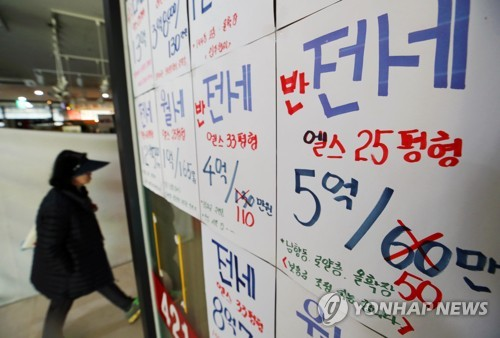 This file photo shows a woman walking past the office of a real estate broker in Seoul. (Yonhap)
