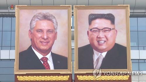 Des images de la Télévision centrale nord-coréenne (KCTV) à Pyongyang montrent d'énormes portraits peints du dirigeant nord-coréen Kim Jong-un (à d.) et du président cubain Miguel Diaz-Canel exposés à l'aéroport international de Sunan le 4 novembre 2018, lorsque le président cubain est arrivé. (Utilisation en Corée du Sud uniquement et redistribution interdite)