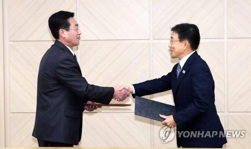 El viceministro de Salud y Bienestar Social de Corea del Sur, Kwon Deok-cheol (dcha.), estrecha la mano de Pak Myong-su, alto cargo del Ministerio de Salud Pública de Corea del Norte, después de firmar un comunicado conjunto, el 7 de noviembre de 2018, en la oficina de enlace intercoreana de Kaesong, en Corea del Norte, tras discutir los esfuerzos conjuntos para luchar contra las enfermedades contagiosas y otras formas de cooperación sanitaria. (Foto del cuerpo de prensa)