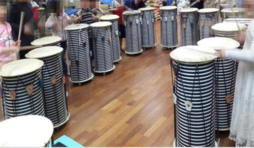 A group of younger North Korean defectors play drums under the music therapy project aimed at helping them better adapt to South Korean society in this photo provided by the Graduate School of Music Therapy of Sookmyung Women's University. (Yonhap)